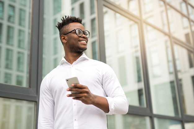 Apuesto joven africano con una camisa blanca con un teléfono en sus manos cerca de un edificio de cristal