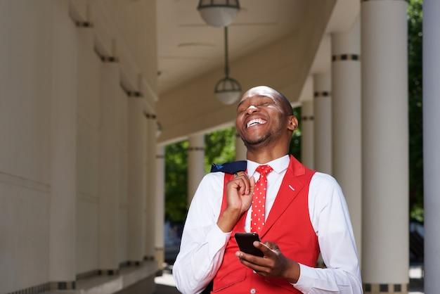Apuesto joven africano en traje riendo al aire libre con teléfono móvil