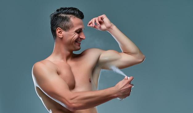 Apuesto joven aislado. retrato de hombre musculoso sin camisa está de pie sobre fondo gris y usando desodorante. concepto de cuidado de los hombres.