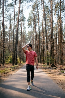 Apuesto joven al aire libre en el parque, caminando en el parque