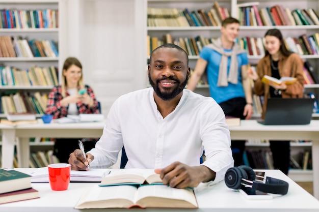 Apuesto joven alegre alegre chico afroamericano con barba, mirando a cámara y sonriendo