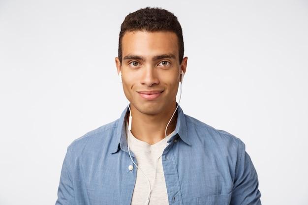 Apuesto joven amable y entusiasta en camisa azul sobre camiseta, escuchando música