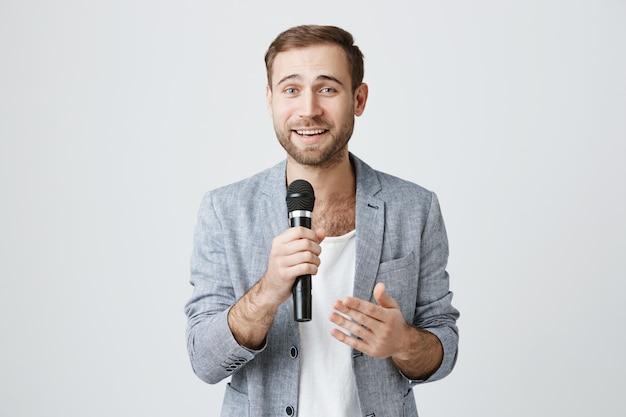 Apuesto joven animador con micrófono, dando un discurso