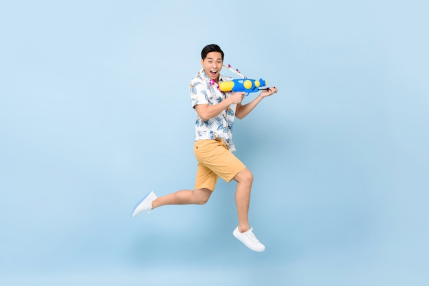 Apuesto joven asiático sonriente jugando con pistola de agua y saltando para el festival songkran en tailandia y el sudeste asiático