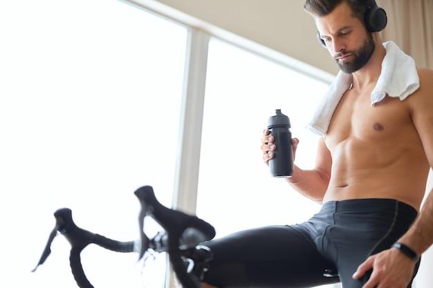 Apuesto joven en auriculares con entrenador de bicicleta en casa
