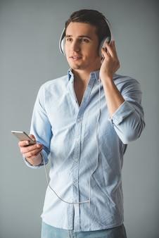 Apuesto joven en auriculares está escuchando música