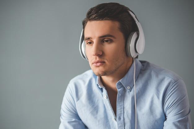 Apuesto joven en auriculares está escuchando música.