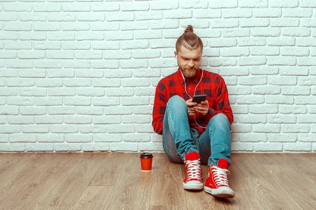Apuesto joven en auriculares con teléfono móvil