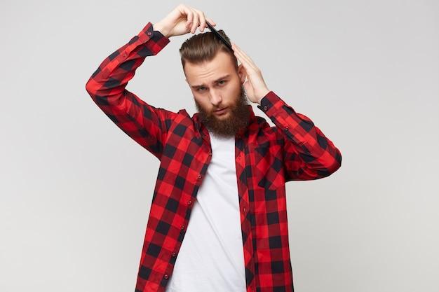 Apuesto joven barbudo en camisa haciendo peinado moderno, arreglando su cabello con peine aislado sobre fondo blanco.