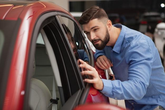 Apuesto joven barbudo examinando el nuevo coche moderno en el concesionario, espacio de copia