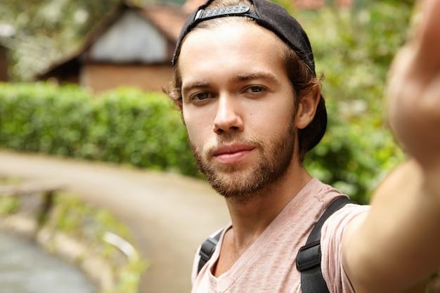 Apuesto joven barbudo con gorra de béisbol al revés tomando selfie, mirando con una sonrisa, posando en country road contra la naturaleza verde