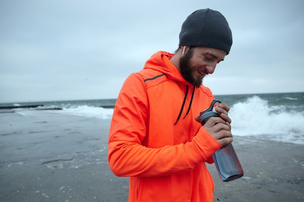 Apuesto joven barbudo de pelo oscuro va a hacer deporte todas las mañanas, va por el paseo marítimo con una botella de fitness en las manos levantadas y sonriendo positivamente. concepto de deporte y estilo de vida saludable