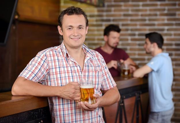 Apuesto joven bebiendo cerveza en el bar y sonriendo.