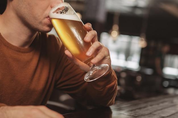 Apuesto joven bebiendo cerveza en el bar