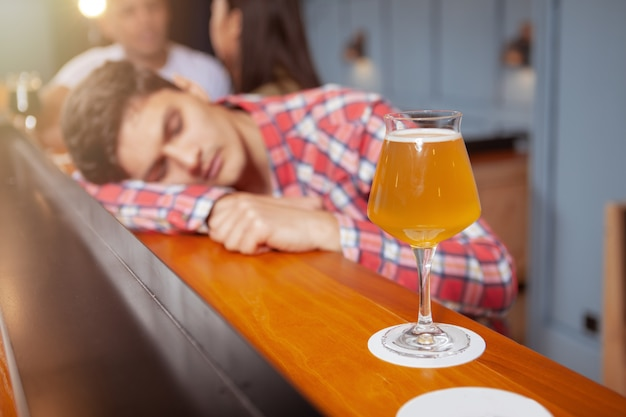 Apuesto joven bebiendo en el pub de cerveza