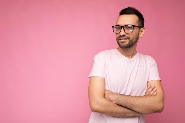 Apuesto joven brunet sin afeitar feliz con camiseta blanca para maqueta y elegantes gafas ópticas aisladas