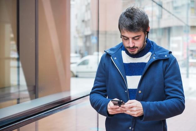 Apuesto joven, caminando en la calle de la ciudad mediante teléfono móvil.