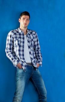 Apuesto joven con camisa a cuadros vaqueros en azul