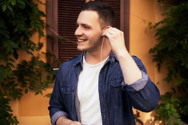 Apuesto joven en una camisa de jeans está escuchando música en los auriculares al aire libre