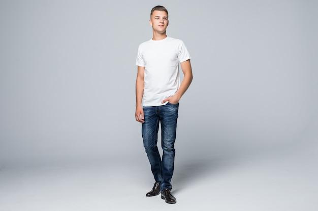 Apuesto joven en una camiseta blanca de ropa de estilo casual y pantalones vaqueros azules en blanco