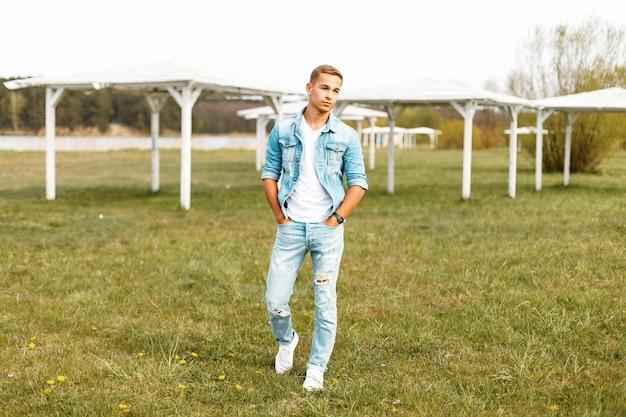 Apuesto joven en una chaqueta vaquera y camiseta blanca con jeans rotos caminando en la naturaleza