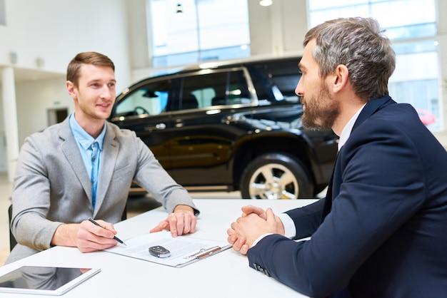 Apuesto joven compra coche de lujo
