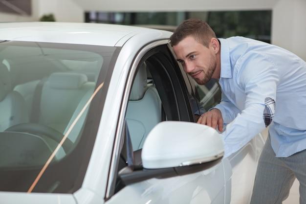 Apuesto joven comprando un auto nuevo en el salón del concesionario