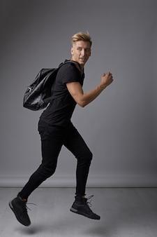Apuesto joven corriendo con una mochila en los hombros