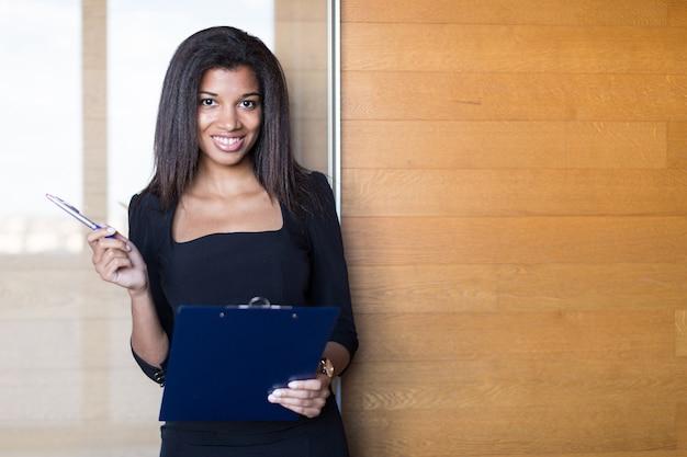 Apuesto joven dama de negocios en negro tableta de retención suite fuerte