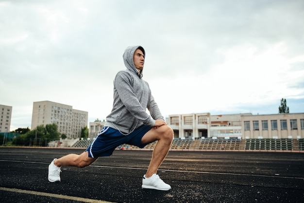 Apuesto joven deportista haciendo estocadas, ejercicios, escuchando música, en el estadio.