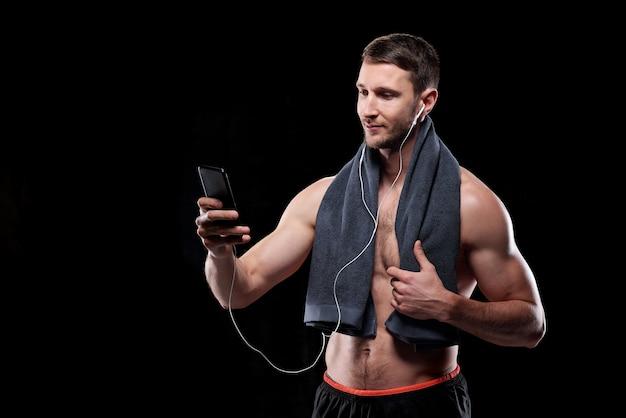 Apuesto joven deportista musculoso sin camisa con una toalla mirando la pantalla del teléfono inteligente mientras se desplaza por la lista de reproducción