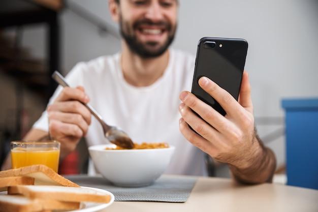 Apuesto joven desayunando mientras está sentado en la cocina, sosteniendo el teléfono móvil