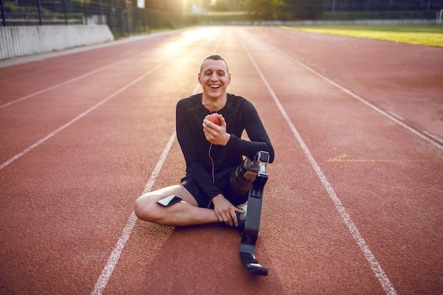 Apuesto joven discapacitado deportivo caucásico sonriente en ropa deportiva y con pierna artificial sentado en la pista, escuchando música y comiendo manzana.