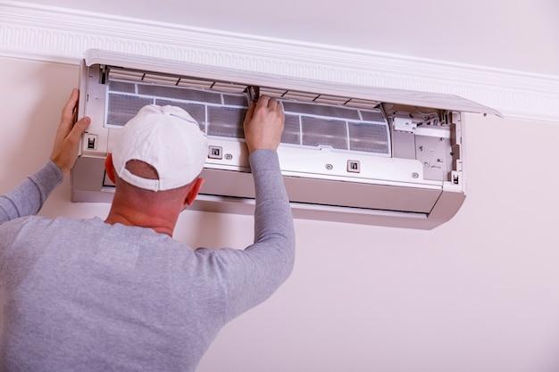 Apuesto joven electricista instalar aire acondicionado en una casa del cliente. limpieza de aire acondicionado. hombre en guantes revisa el filtro.