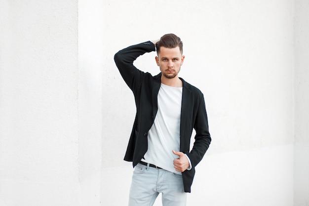 Apuesto joven elegante con una chaqueta de moda negra y una camiseta blanca posando junto a una pared blanca