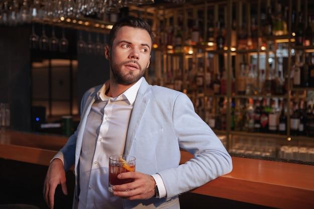 Apuesto joven elegante relajante en el bar de cócteles, apoyándose en la barra de bar, espacio de copia