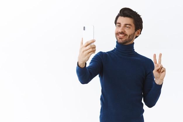 Apuesto joven elegante vestido con un suéter de cuello alto de moda para la fiesta de navidad, tomando selfie para publicar en línea, sosteniendo un teléfono inteligente, haciendo un gesto de paz y sonriendo linda pared blanca