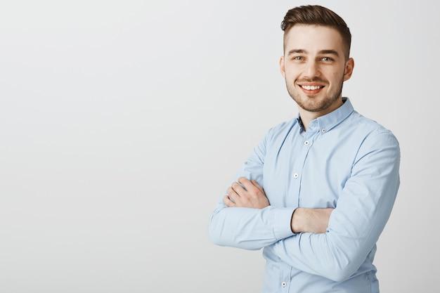 Apuesto joven empresario con brazos cruzados sonriendo confiado
