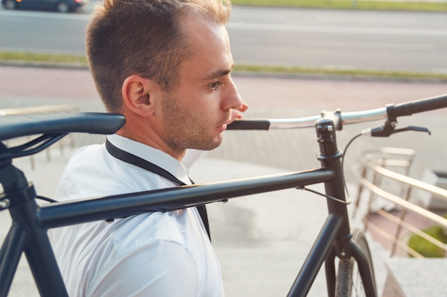 Apuesto joven empresario en una camisa blanca y corbata negra lleva su bicicleta