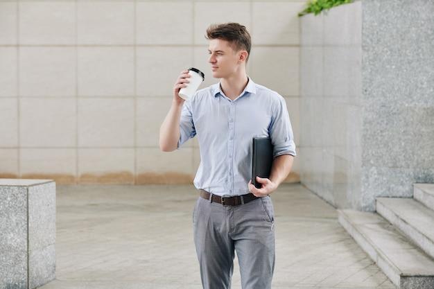 Apuesto joven empresario con carpeta de documentos de cuero y una taza de café para llevar caminando al aire libre