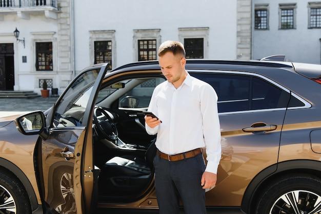 Apuesto joven empresario hablando por teléfono mientras está de pie cerca de su automóvil al aire libre