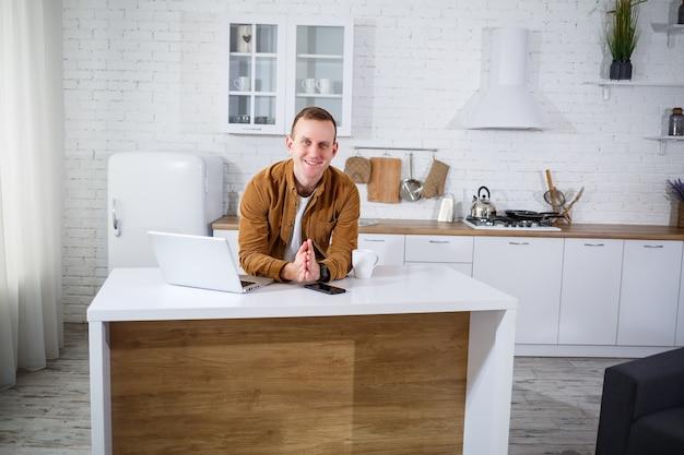 Apuesto joven empresario que trabaja con la computadora de forma remota sentado en la mesa de la cocina. una persona agradable y feliz se comunica en una red social, busca información en internet.