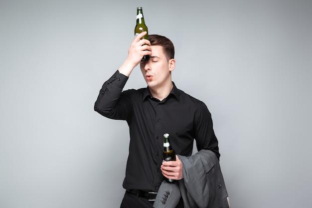 Apuesto joven empresario en reloj costoso y camisa negra sostienen chaqueta gris y cerveza
