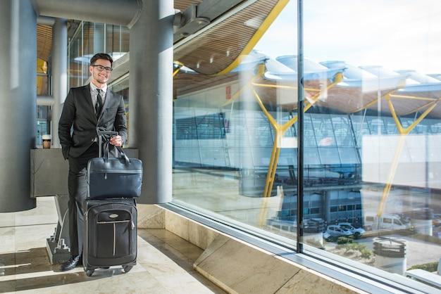Apuesto joven empresario sonriendo junto a la ventana con su equipaje esperando su vuelo