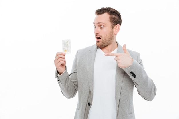 Apuesto joven empresario sorprendido señalando mientras sostiene la tarjeta de crédito.