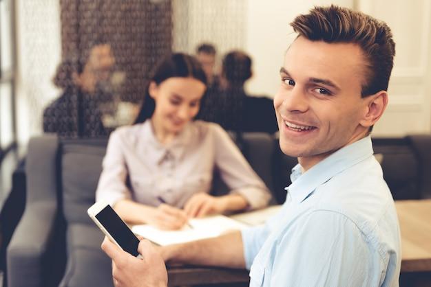 Apuesto joven empresario está utilizando un teléfono inteligente