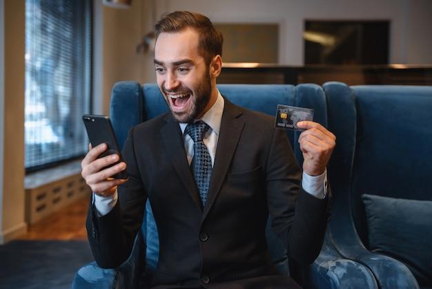 Apuesto joven empresario vistiendo traje sentado en el vestíbulo del hotel, mediante teléfono móvil, mostrando tarjeta de crédito plástica