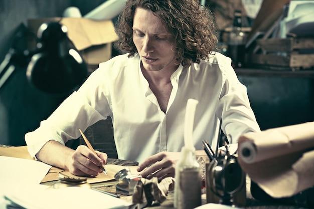 Apuesto joven escritor sentado en la mesa y escribiendo algo en su bloc de dibujo en casa