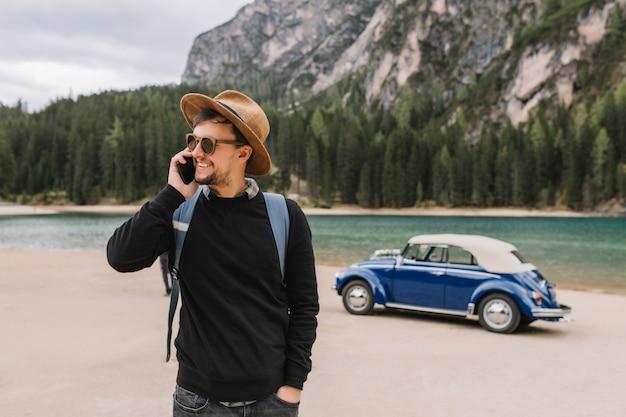 Apuesto joven esperando amigos junto al coche retro en la orilla del río, hablando con ellos por teléfono y mirando a su alrededor