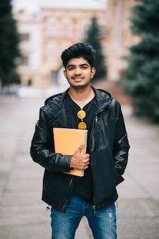 Apuesto joven estudiante indio hombre sosteniendo portátiles mientras está de pie en la calle